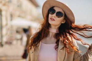Good-looking european woman in black sunglasses plays with curly ginger hair. Outdoor photo of carefree red-haired female model in elegant hat walking down the street.